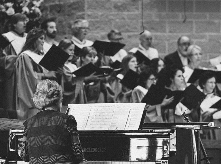 Woman playing piano with choir